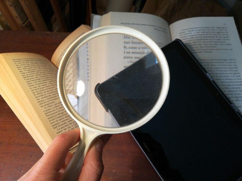 Lente d'ingrandimento sopra un tablet e un libro